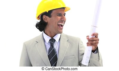 Happy engineer holding blueprints against a white background