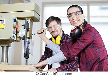 happy engineer instructing female apprentice on use of drill