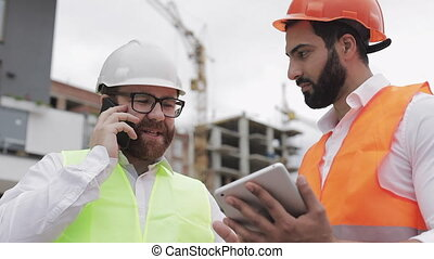 Happy engineer speaks on Mobile phone on construction site and checks the work of the worker. Builder talks on smartphone. Checking the construction phase