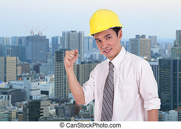 Happy engineer with arm raised, concept of successful, city background
