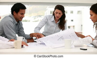 Happy engineers working on plans standing around a table in...