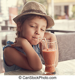 Happy enjoying kid girl drinking tasty natural smoothie juice with closed relaxed eyes in street restaurant