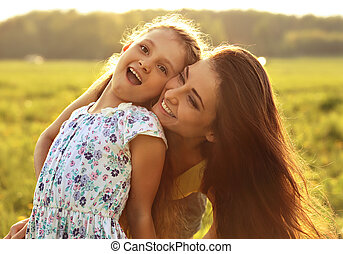 Happy enjoying mother hugging her laughing excited kid girl on sunset bright summer background. Closeup portrait.