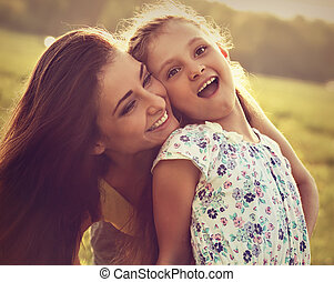 Happy enjoying mother hugging her laughing excited kid girl on sunset bright summer background. Closeup toned emotional portrait.