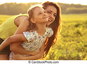 Happy enjoying mother hugging her playful laughing kid girl on sunset bright summer background. Closeup portrait.