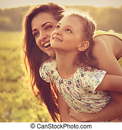 Happy enjoying mother hugging her playful laughing kid girl on sunset bright summer background. Closeup toned portrait.