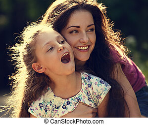 Happy enjoying mother hugging her relaxing smiling kid girl on bright summer background. Closeup toned portrait