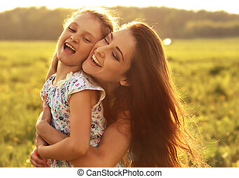 Happy enjoying smiling mother hugging her playful laughing kid girl on sunset bright summer background. Closeup portrait