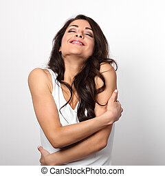 Happy enjoying woman hugging herself with natural emotional face on white background. Love concept of yourself