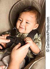 happy ethnic Asian baby boy child put in carseat - Smiling...
