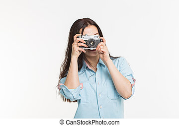 Happy european female model with dark hair enjoying indoor photoshoot. Young woman is taking a photo on white background.