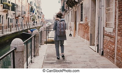 Happy European female travel blogger taking smartphone photo walking along famous water canal street in Venice Italy.