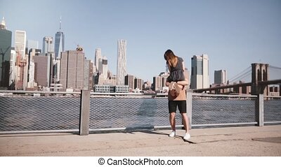 Happy European man holding his girlfriend in arms and spinning at epic Manhattan view in New York City slow motion.