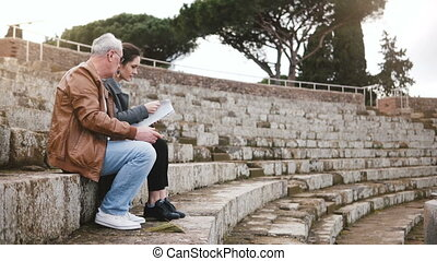 Happy European senior man and young woman sitting on old...