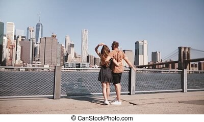 Happy European tourist couple stand hugging, arms raised enjoying epic Manhattan view in New York, USA slow motion.