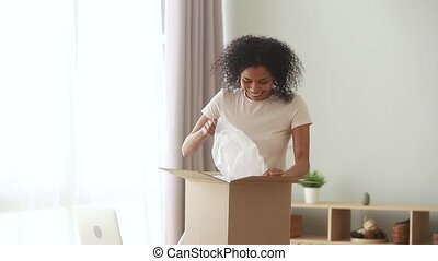 Happy excited african american woman customer open parcel at...