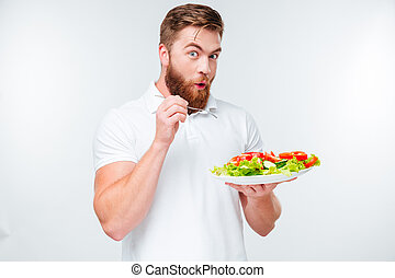 Happy excited bearded man holding plate with fresh sala a,