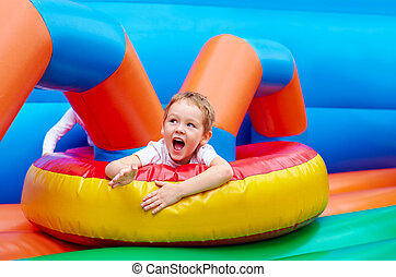 happy excited boy having fun on inflatable attraction...