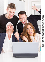 happy excited business people colleagues winning online looking at laptop computer smiling with clenched fists
