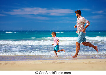 happy excited father and son running on summer beach, enjoy life