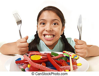 happy excited Latin female child holding fork and knife sitting at table ready for eat a dish full of candy