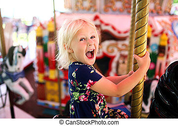 Happy Excited Little Girl Riding the Carousel at a Carnival