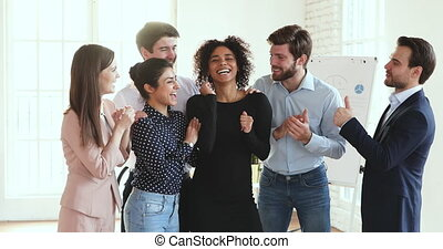 Overjoyed young multiracial colleagues congratulating african american female team leader with business success. Happy excited multiracial teammates feeling excited of corporate achievement in office.