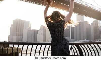 Happy excited playful young woman spinning near river embankment fence with raised arms, smiling at camera slow motion.