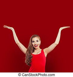 Happy excited surprised woman in red dress having fun on red colorful bright background. Girl with empty hands up