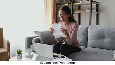 Happy excited woman reading letter sitting on sofa at home