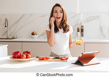 Happy excited woman talking on mobile phone while cooking in...