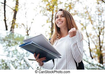 Happy excited woman with notebook standing and celebrating success outdoors