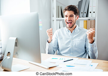 Happy excited young businessman sitting and celebrating success