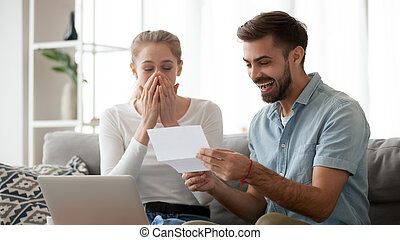 Happy excited young couple receiving unexpected good news