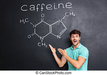 Happy excited young scientist showing chemical structure of caffeine molecule