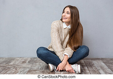 Happy excited young woman sitting with legs crossed