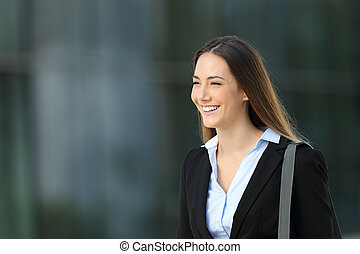 Happy confident executive walking on the street with an office building in the background