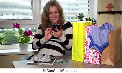 Happy expectant mother with phone after successful shopping...