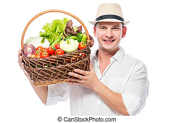 Happy experienced farmer with a harvest of vegetables in a basket on a white background