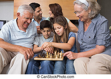 Happy extended family playing chess