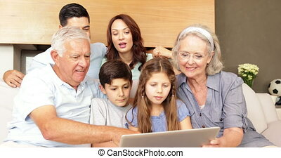 Happy extended family using a laptop