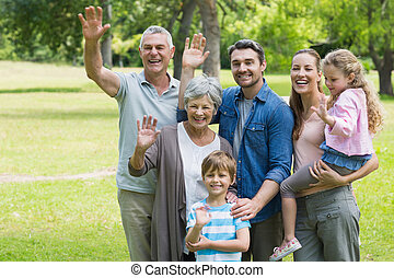 Happy extended family waving hands at park