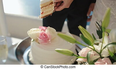 Happy fabulous couple puts a piece of wedding cake on the plate with holding hands.