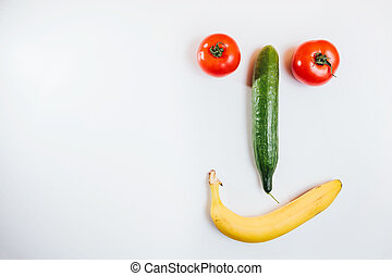 Happy face made with fresh fruits. Tomato, cucumber , banana.