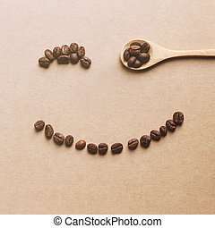 Happy face shaped of coffee beans with wooden spoon, retro filte