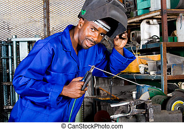 happy factory worker - man welding in factory and smiling
