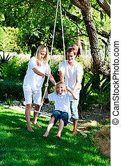 Happy familiy having fun swinging