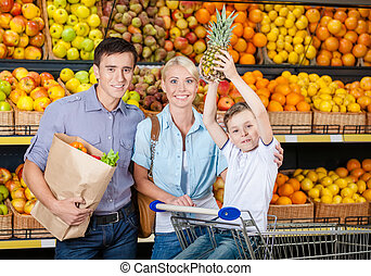 Happy family against shelves of fruits has shopping
