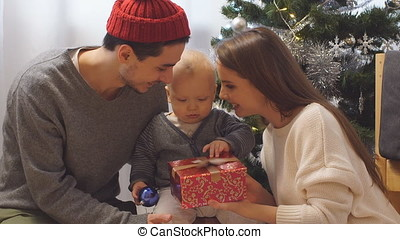 Happy Family and Baby with Christmas Gift near the Christmas Tree at home. Child opening a Gift Box.