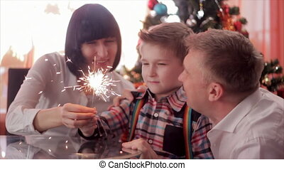 Happy family and Bengal fire. Mother holding sparkler, then she and father kissing child while he looking at light. Slow motion